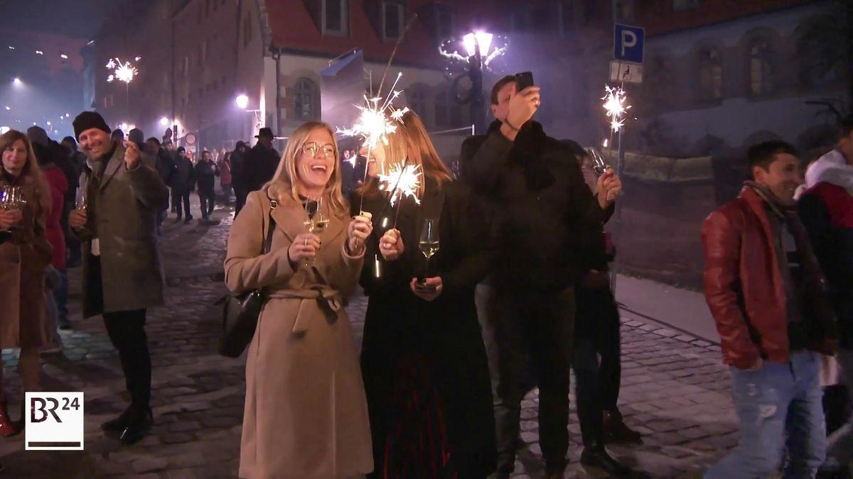 Zwei Frauen in Nürnberg halten anlässlich des Jahreswechsels Wunderkerzen und Weingläser in der Hand