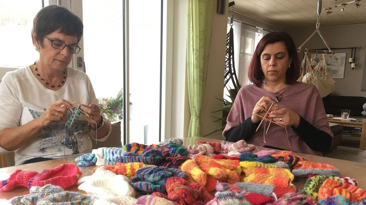 Zwei Frauen sitzen an einem Tisch und stricken.
