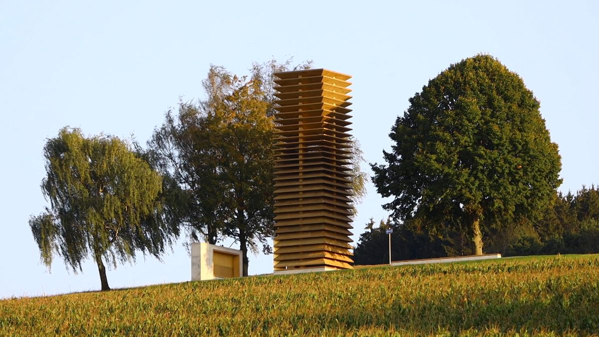 Turm aus Holzlamellen in einer grünen Landschaft