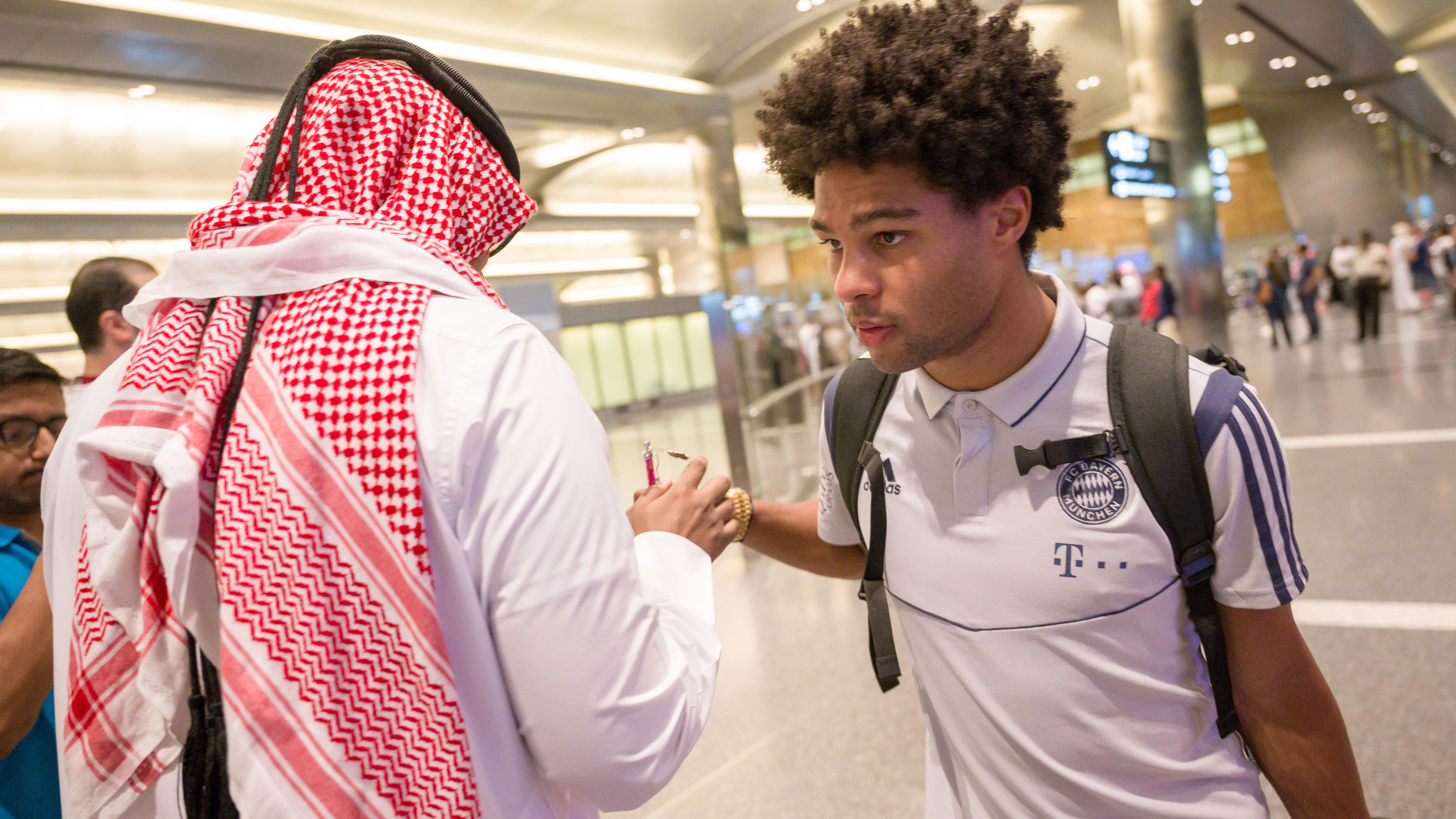 Bayern-Spieler Serge Gnabry wird nach der Ankunft der Mannschaft auf dem Flughafen von Katar von Fans empfangen.