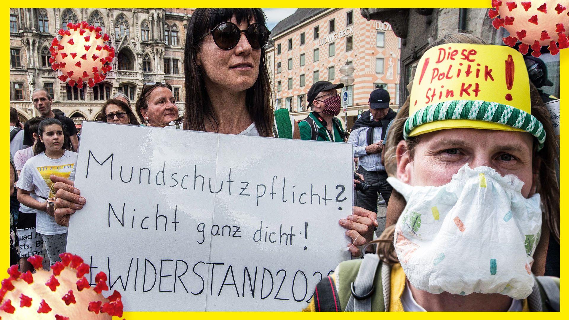 """Menschen auf dem Münchner Marienplatz. Eine Frau hält ein Schild, auf dem steht: """"Mundschutzpflicht? Nicht ganz dicht! #Widerstand2020"""". Ein Mann trägt eine Windeln vor Mund und Nase, an seine Stirn ist ein Schild angebracht mit der Aufschrift: """"Diese Politik stinkt!"""""""
