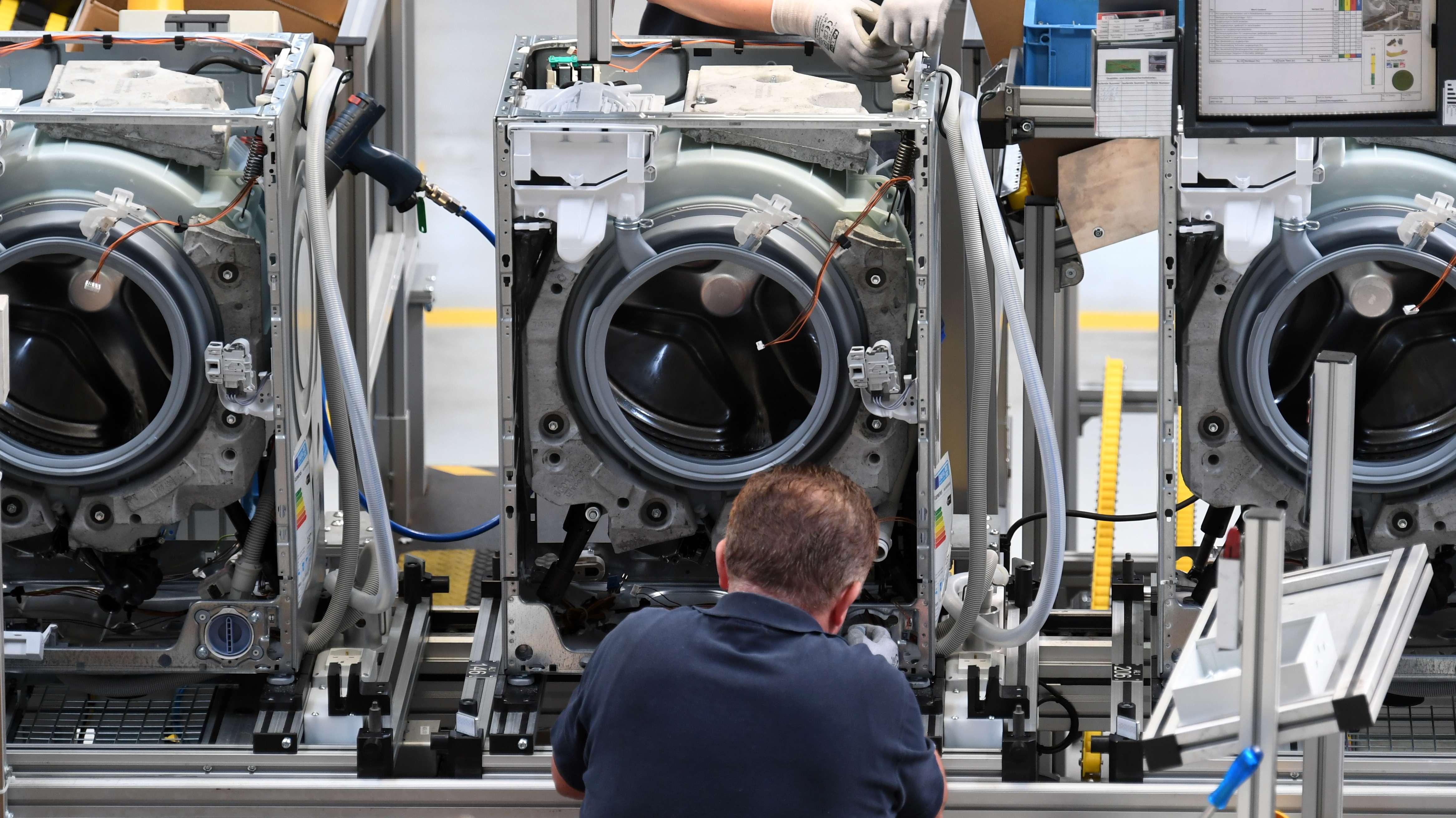 Ein Mitarbeiter von Bosch arbeitet an einer Waschmaschine