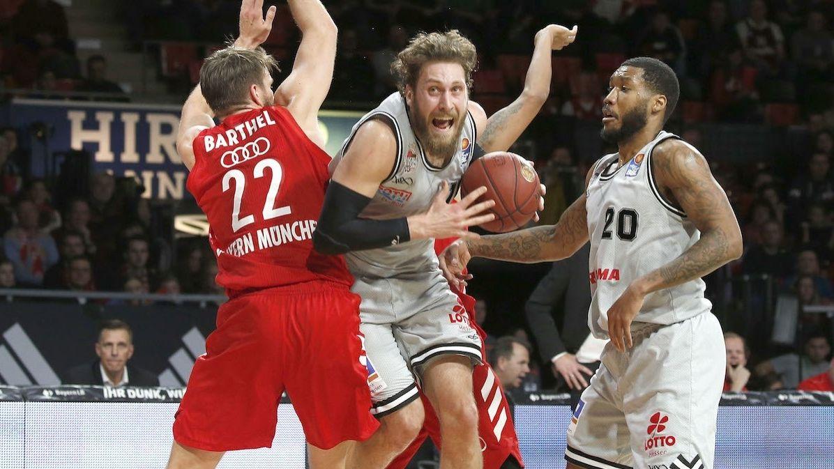 Der Basketball-Spieler Matthew Tiby mit Bart und im weißen Trikot kämpft sich an zwei Gegenspielern vorbei.