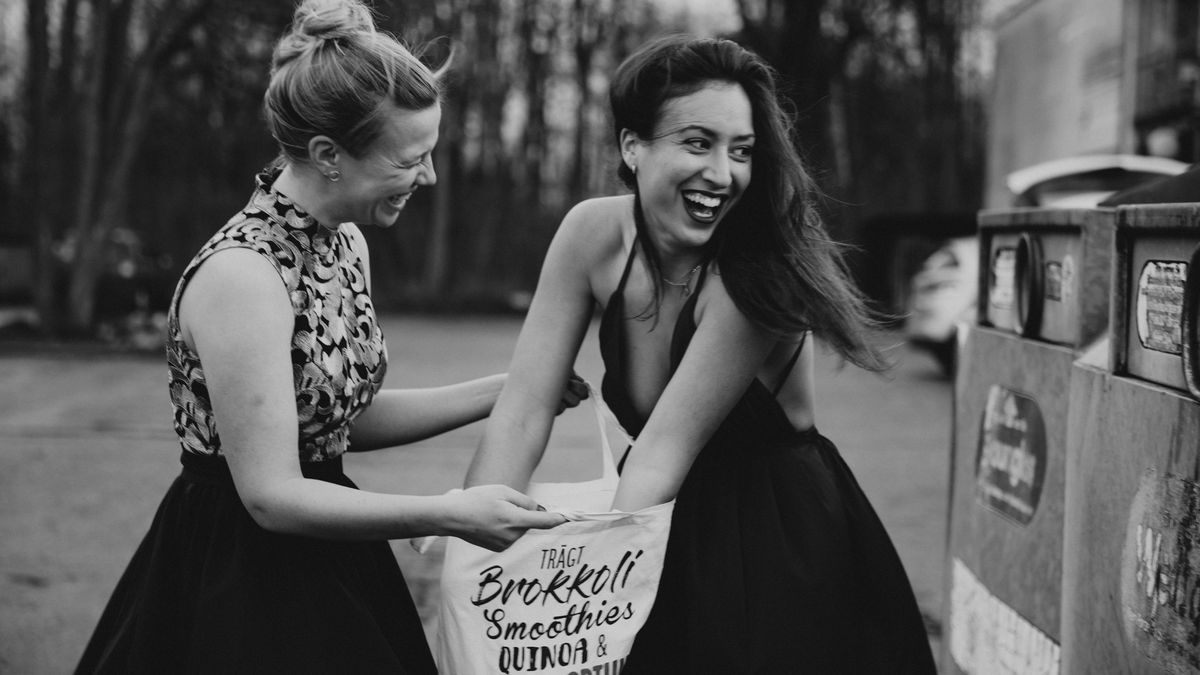 Zwei Frauen an einem Flaschencontainer in schicken Abendkleidern.