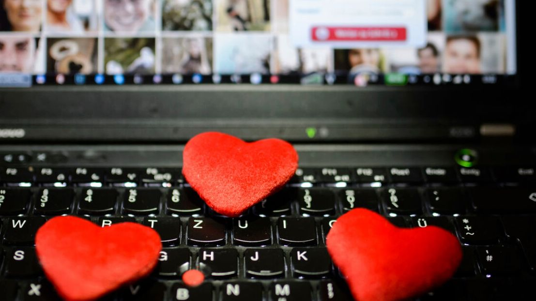 Rote Herzen liegen auf der Tastatur eines Notebooks, im Hintergrund ist die Webseite einer Internet-Partnerbörse zu sehen