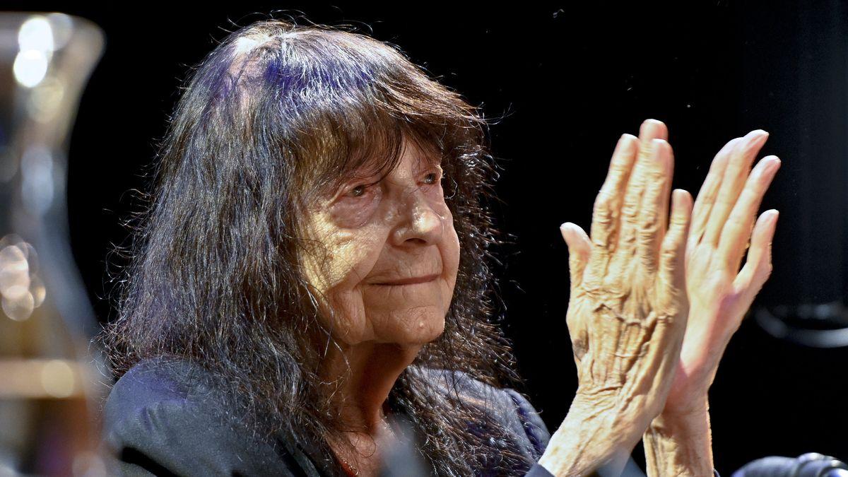 Farbporträt von Friederike Mayröcker, die applaudierenden Hände im Vordergrund
