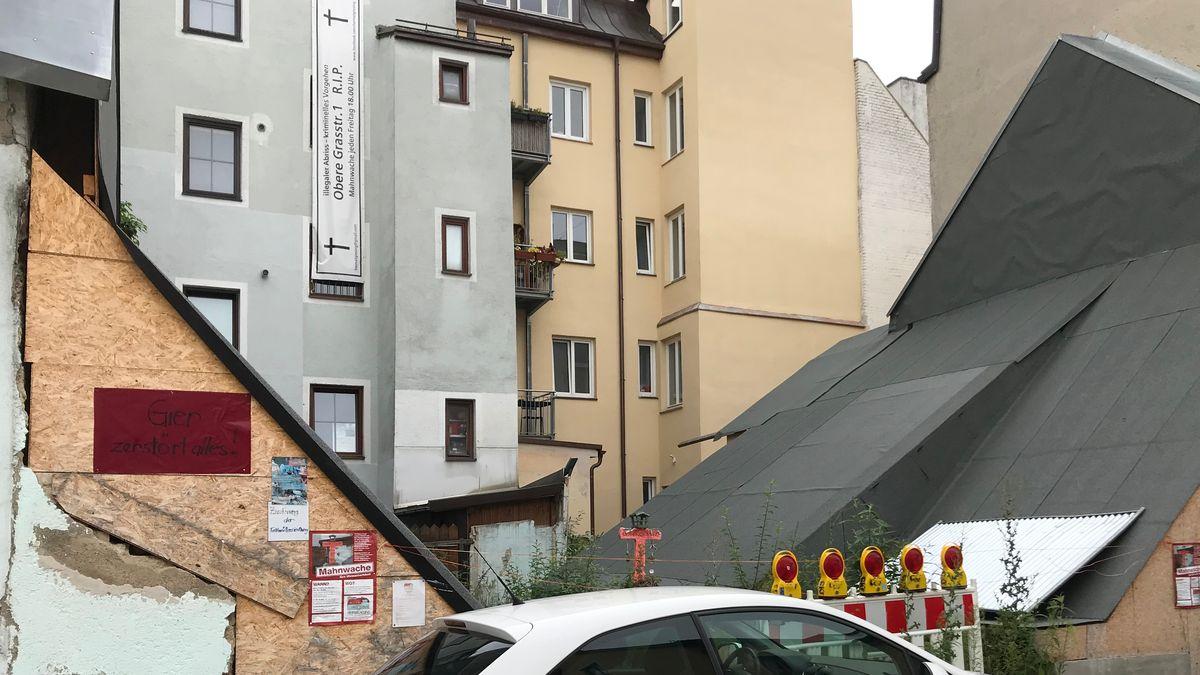 """Juli 2019: Die Abrissstelle in München-Giesing, wo einst das Uhrmacherhäusl stand - daneben ein Schild mit der Aufschrift """"Gier ändert alles""""."""