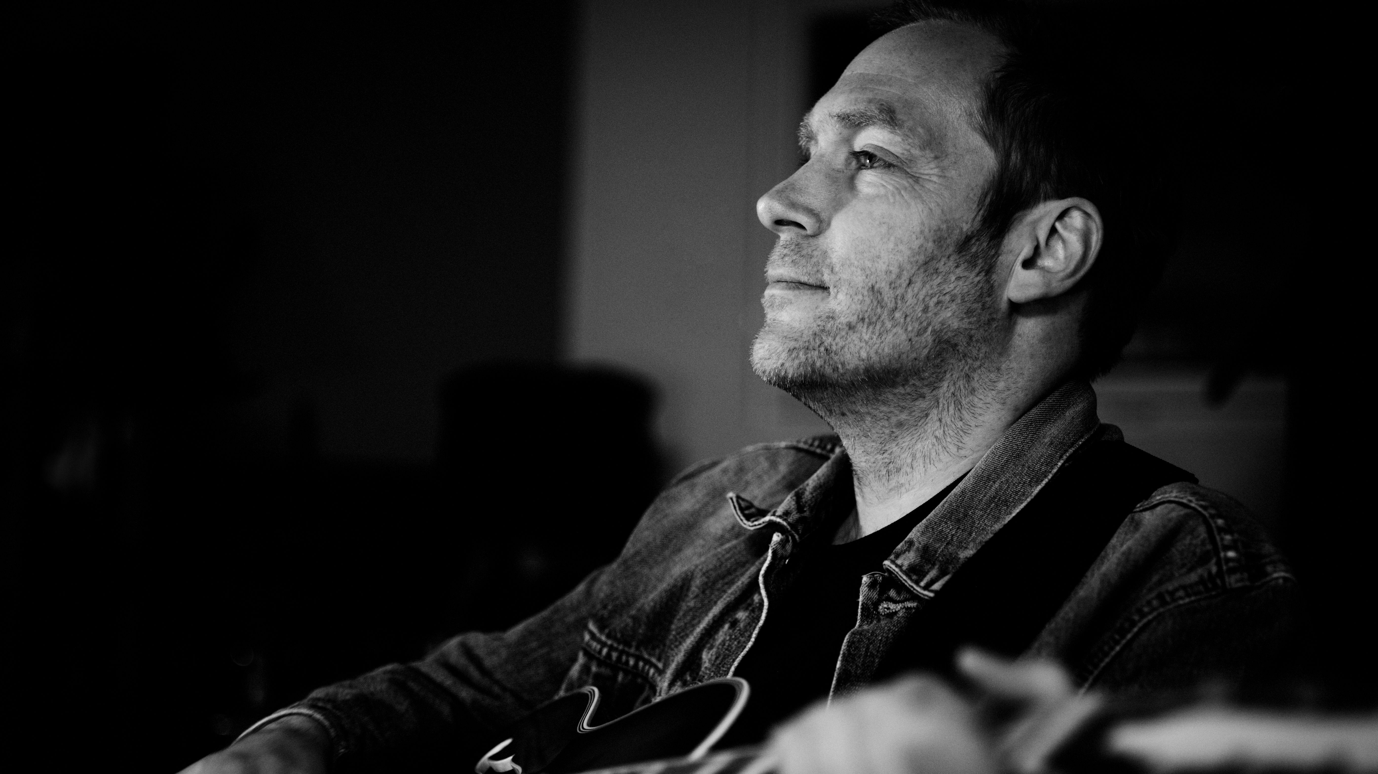 Thees Uhlmann lächelt zufrieden mit der Gitarre in der Hand