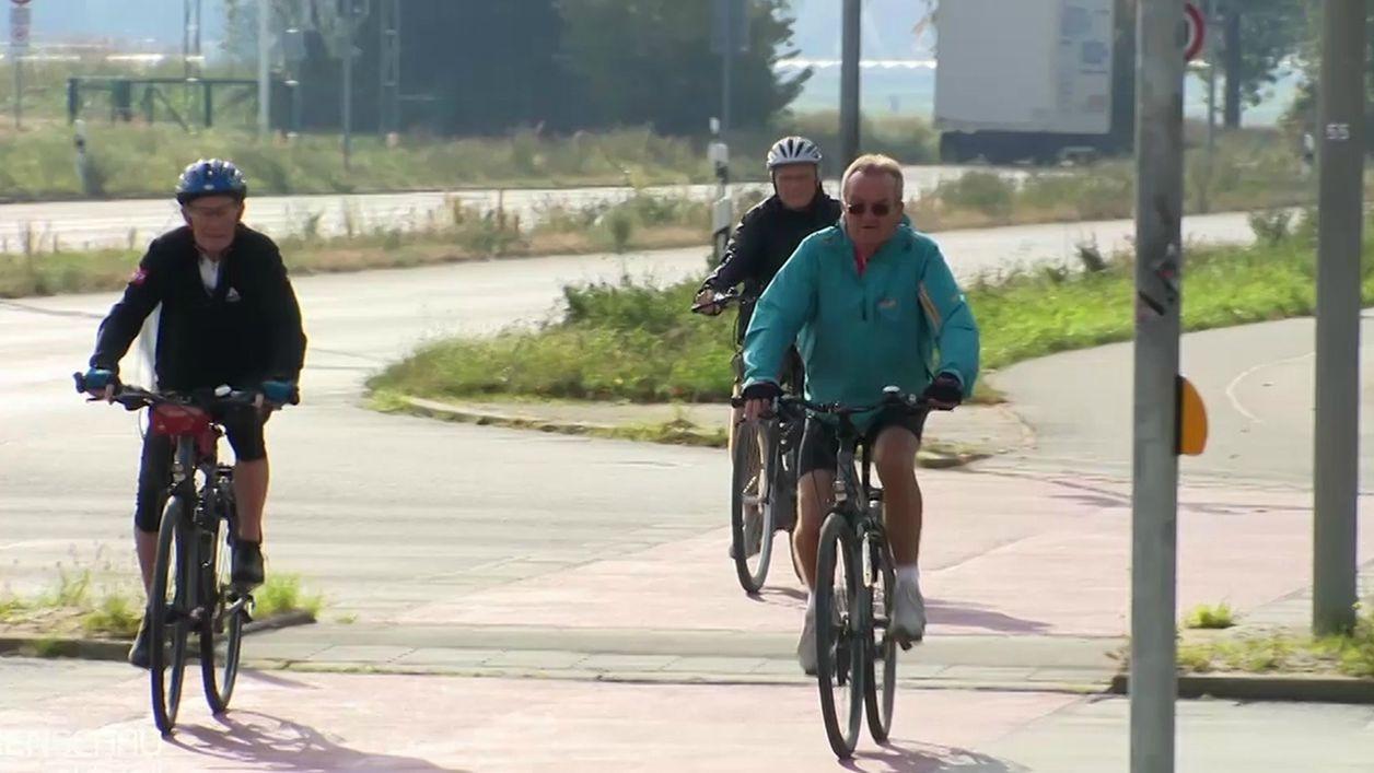 Fahrradfahrer fahren auf dem Radweg neben einer Straße