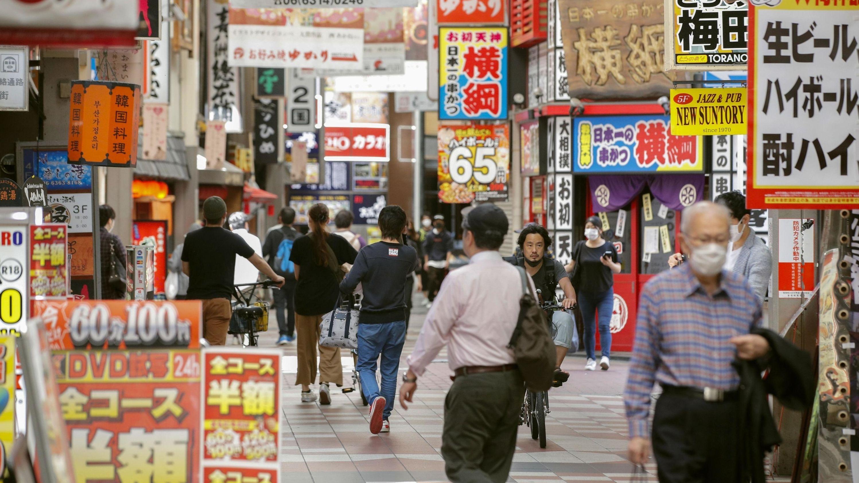 Menschen gehen durch eine Einkaufsstraße in Osaka, nachdem die Geschäfte wieder öffnen konnten.