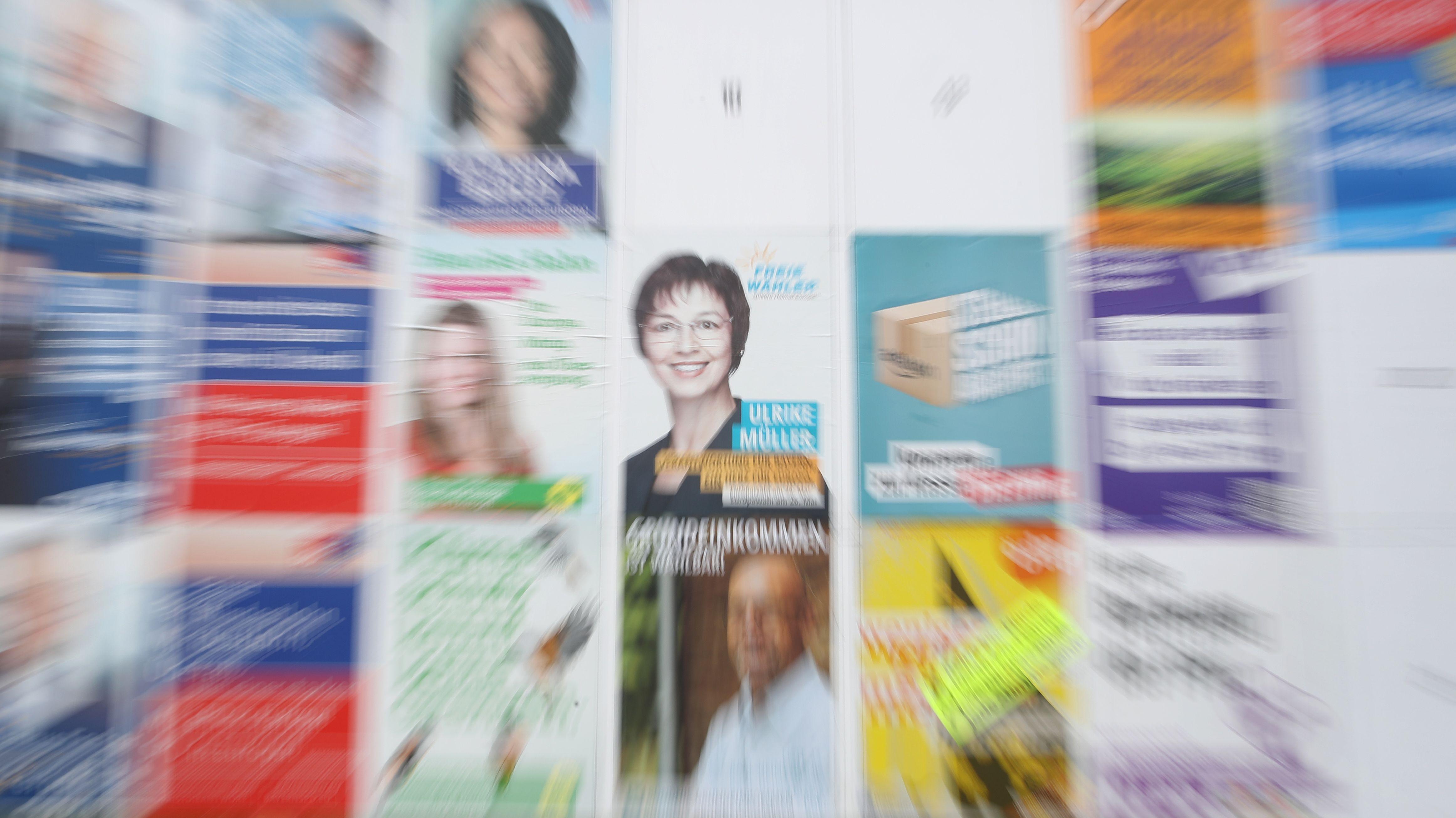 Eine Plakatwand mit Wahlplakaten.