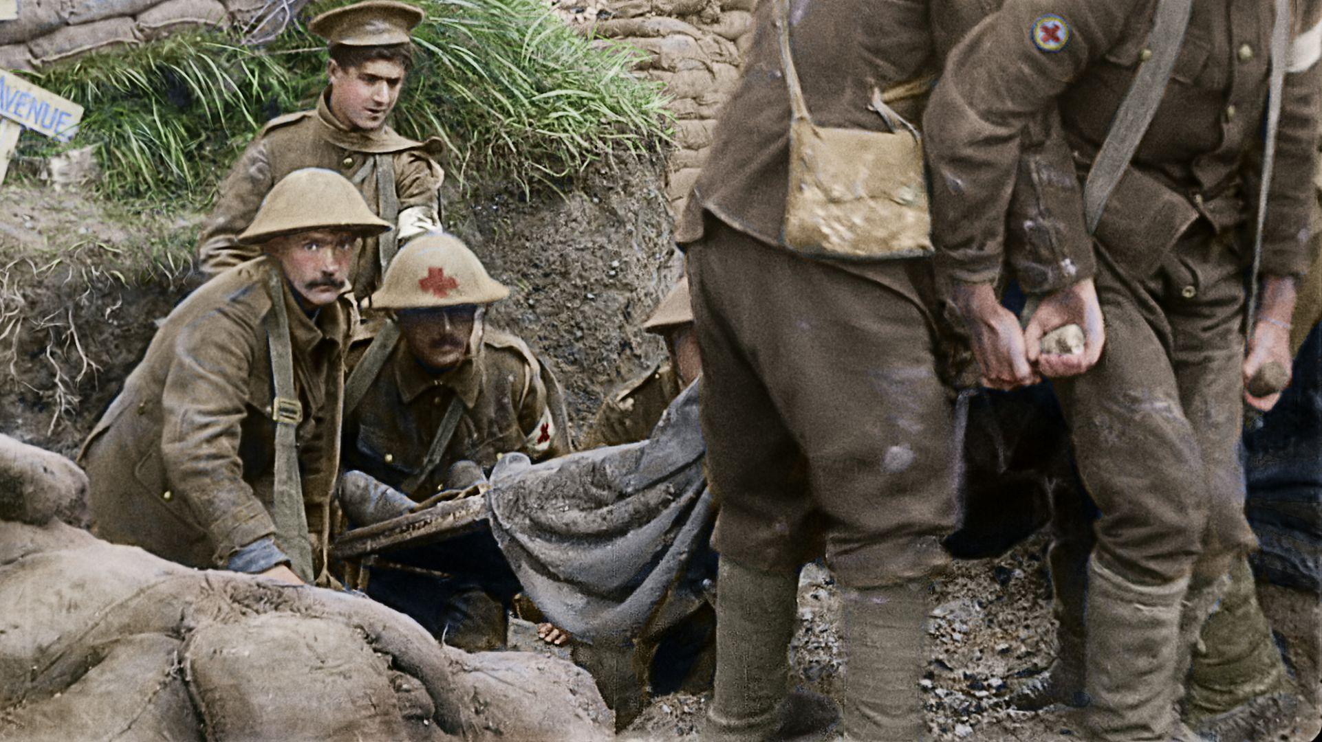 Das Bild zeigt, wie ein verwundeter Soldat aus einem Schützengraben des Ersten Weltkriegs abtransportiert wird.