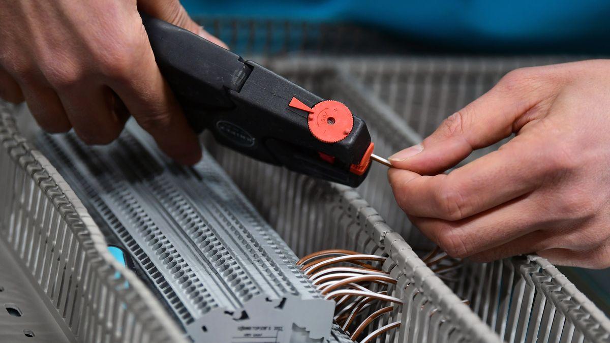 Nahaufnahme eines Mechatronikers. Seine Hände entfernen mit einer speziellen Zange die Isolierung von einem Draht.