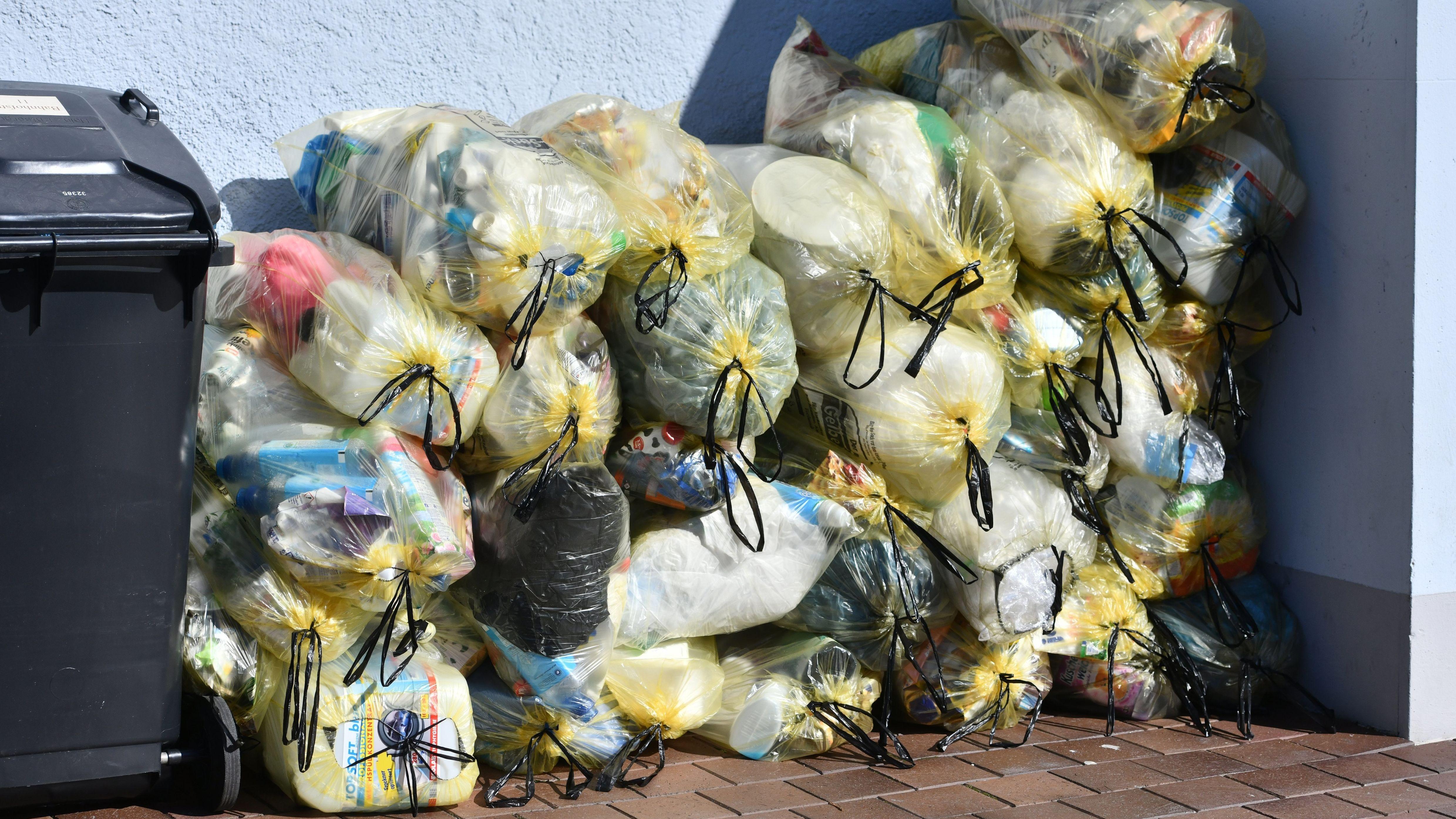Gelbe Säcke mit Kunststoff-Abfällen stapeln sich am Straßenrand, aufgenommen am 20. März 2019 in Freising