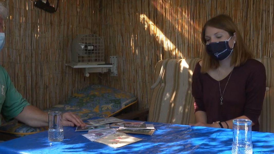 Nina Eidenberger sitzt mit Mundschutz an einem Tisch