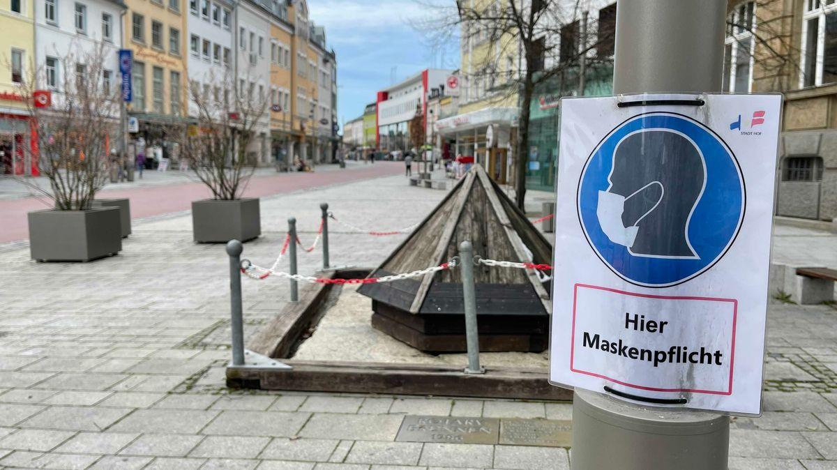 """An einem Pfosten ist ein Schild mit der Aufschrift """"Hier Maskenpflicht"""" angebracht, dahinter eine Fußgängerzone."""