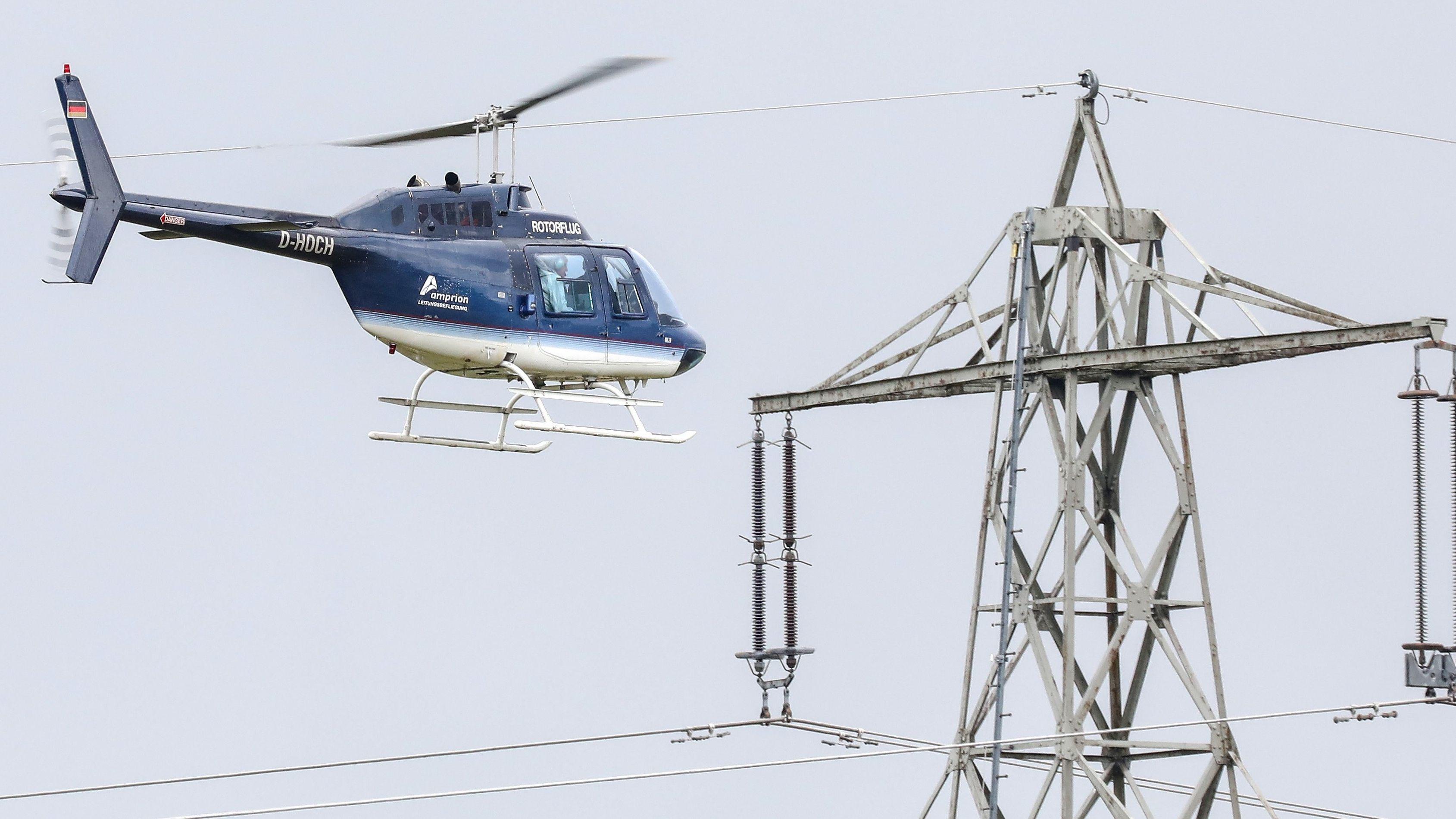 Hubschrauber-Crew inspiziert Strommast