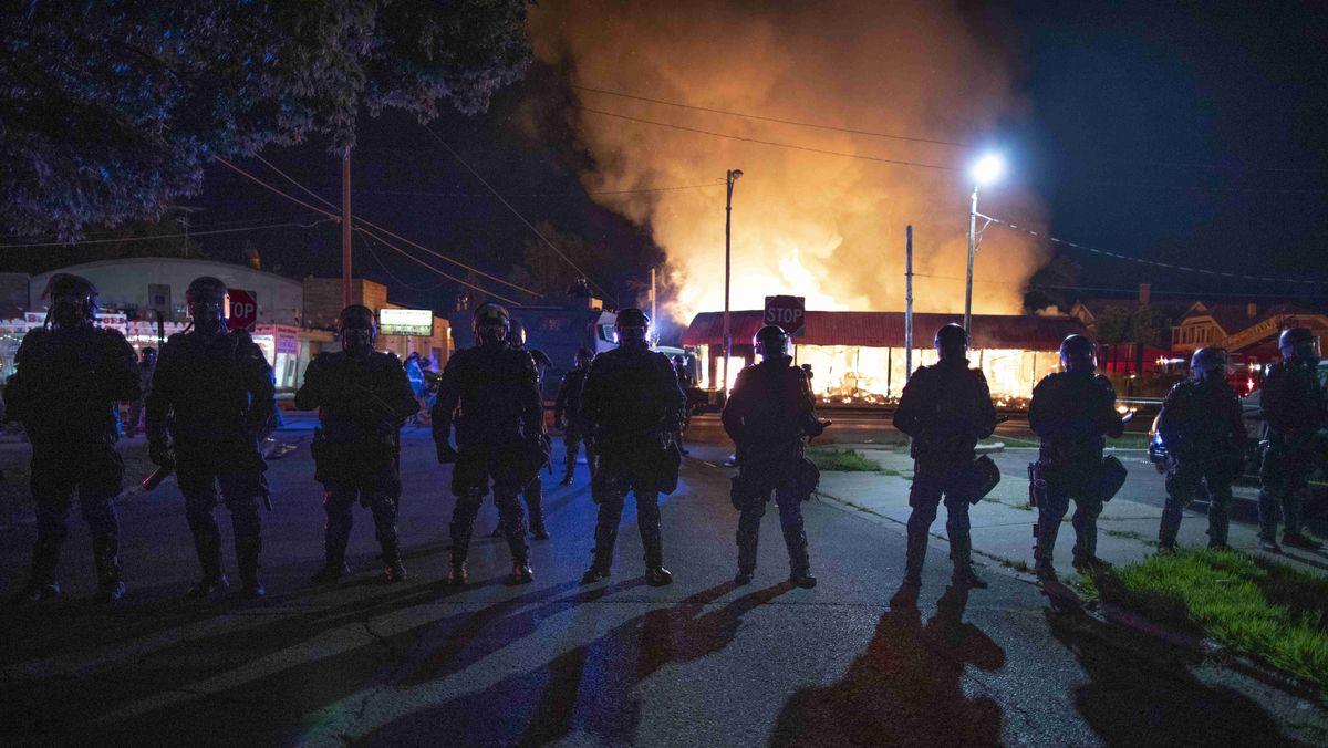 Kenosha im August 2020: Eine Reihe von Polizisten steht vor einem brennenden Gebäude.