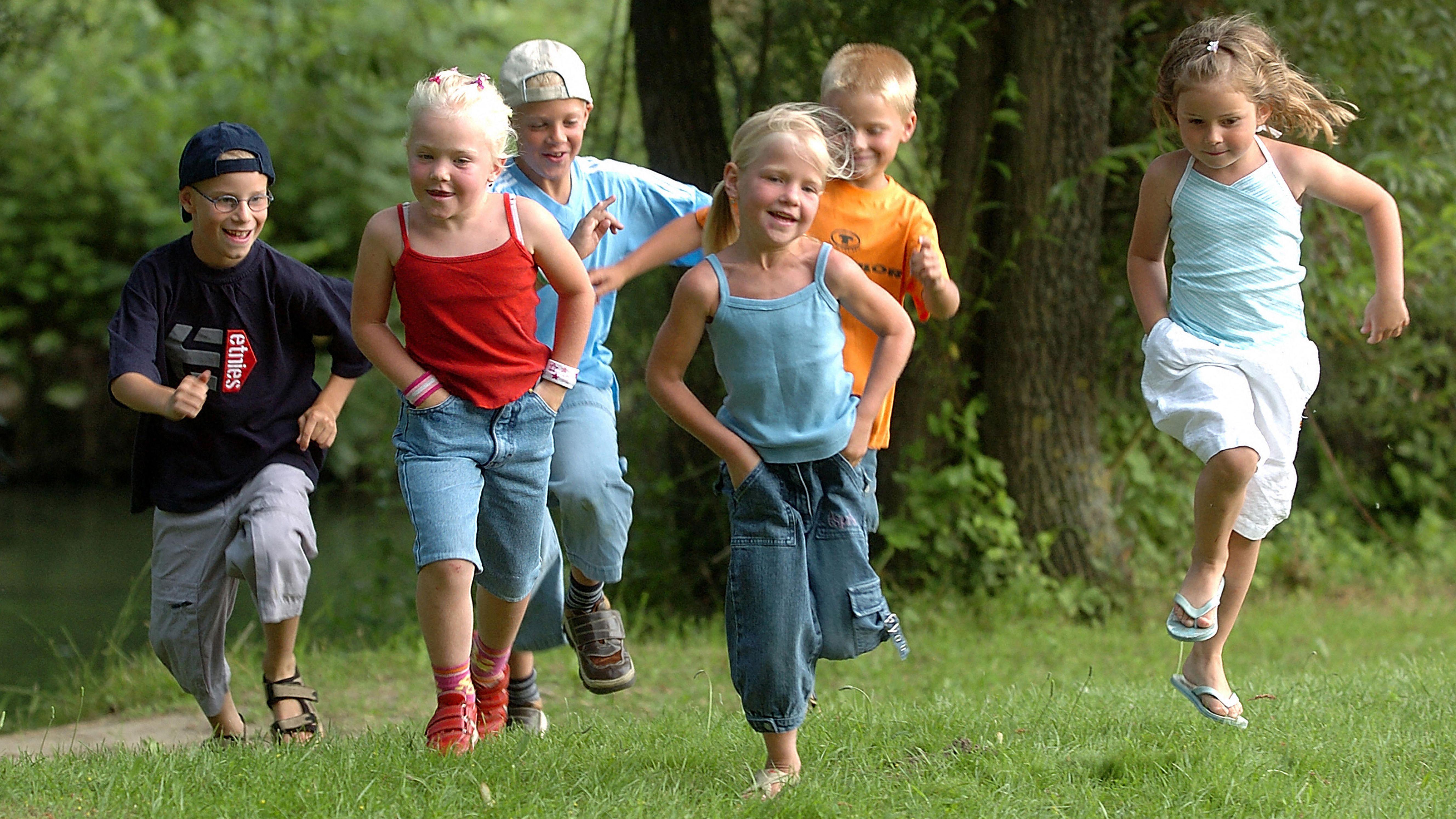 Kinder laufen in einem Park über eine Wiese