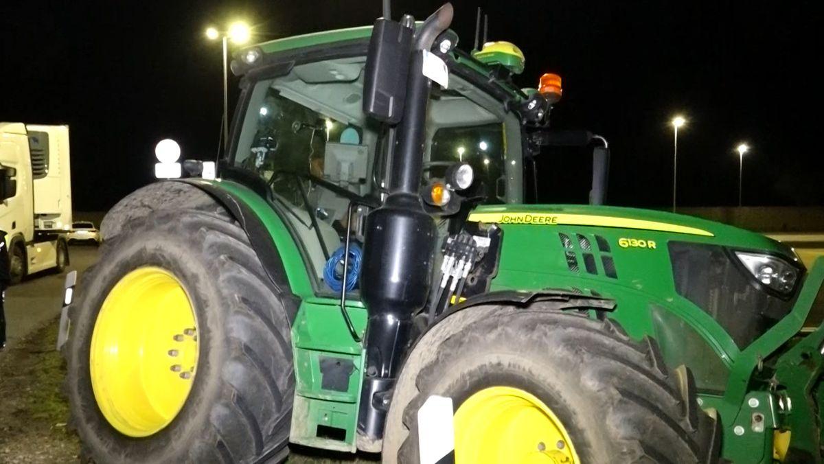 Ein Traktor steht nachts auf einem Grünstreifen.