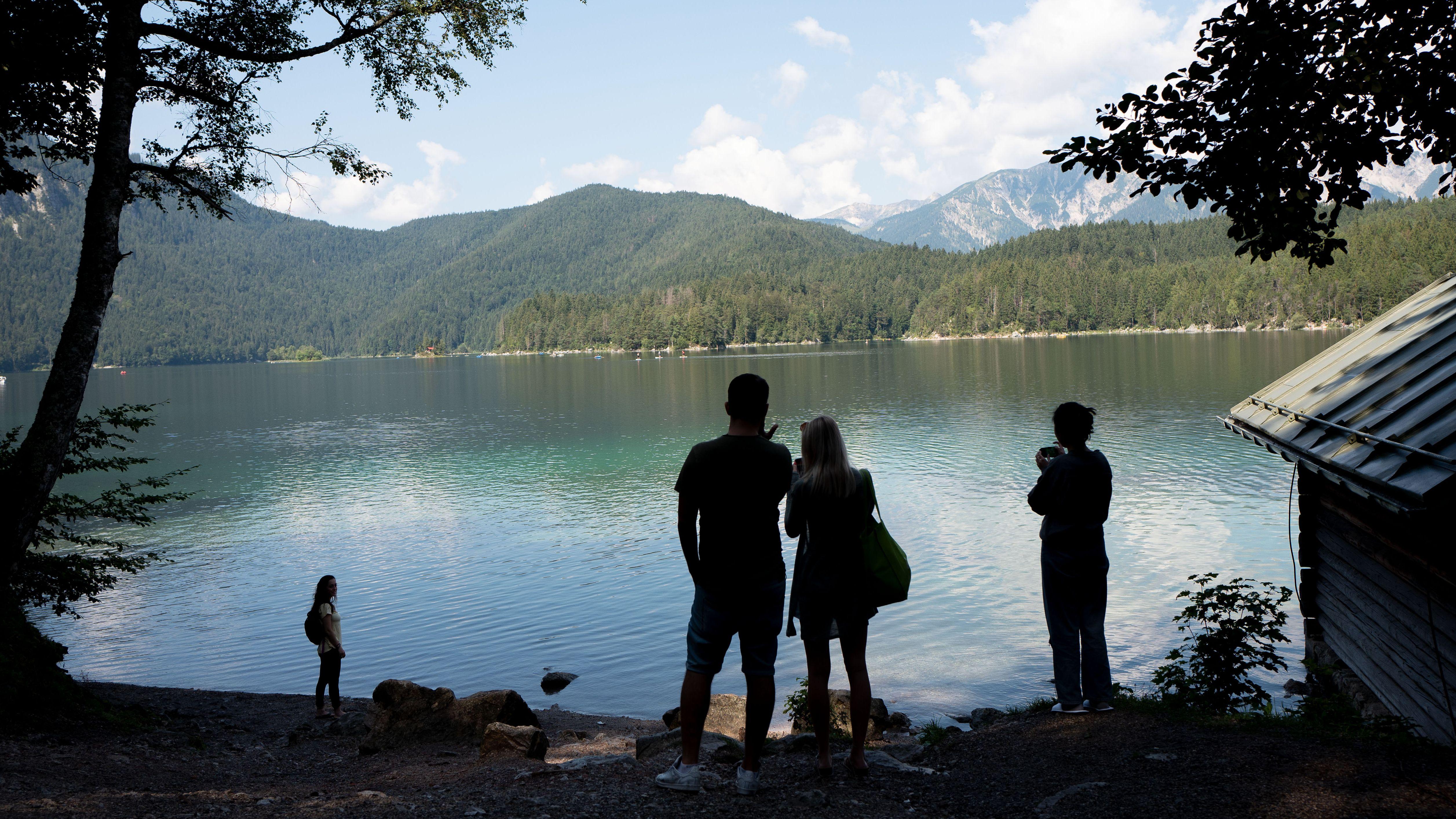 Menschen am Ufer des Eibsees, im Hintergrund das Wettersteingebirge.