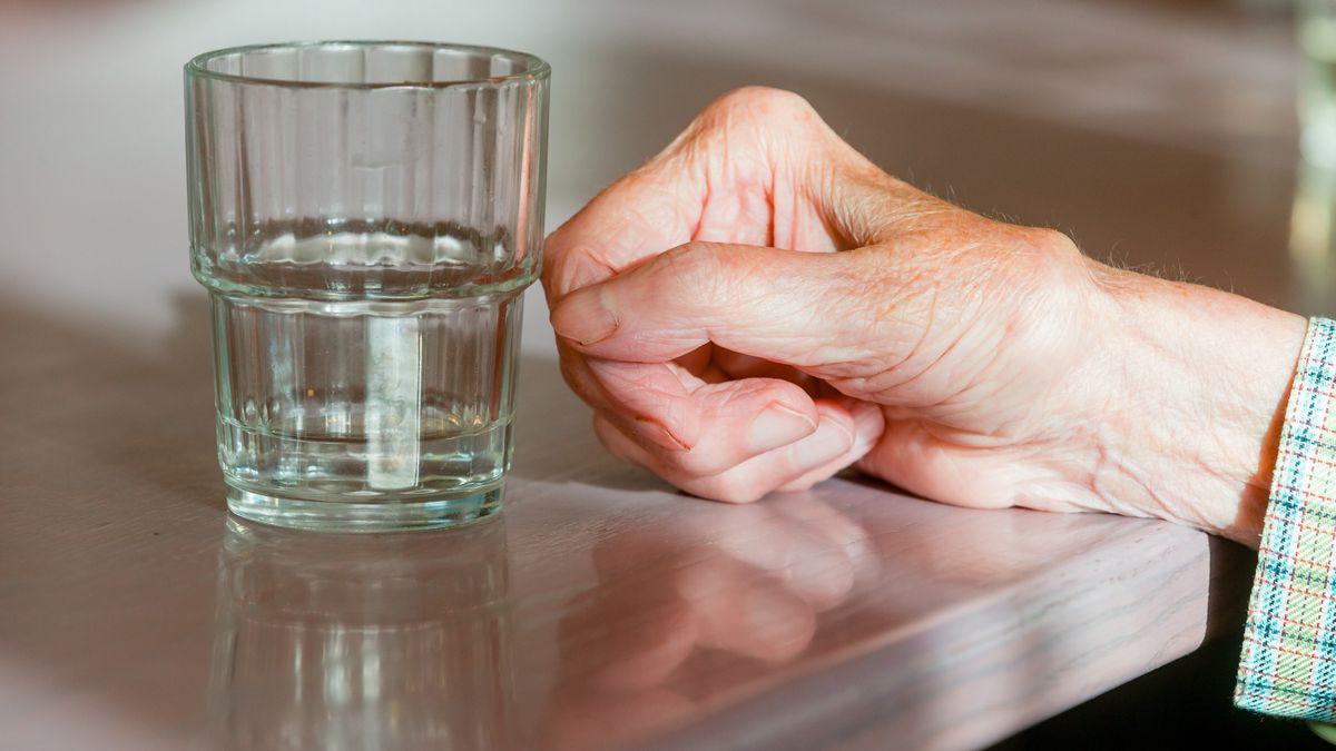 Die Hand einer Seniorin liegt auf einem Tisch.