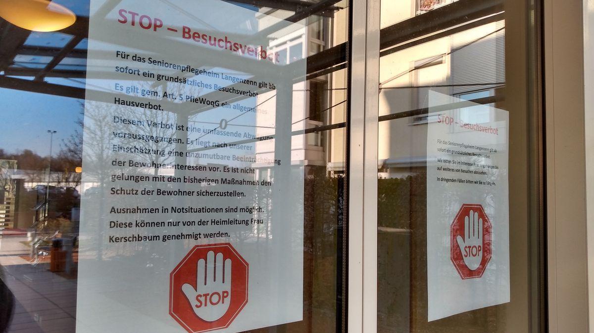 Zwei Zettel mit Informationen zum Besuchsverbot kleben an der Eingangstür zum Seniorenheim in Langenzenn