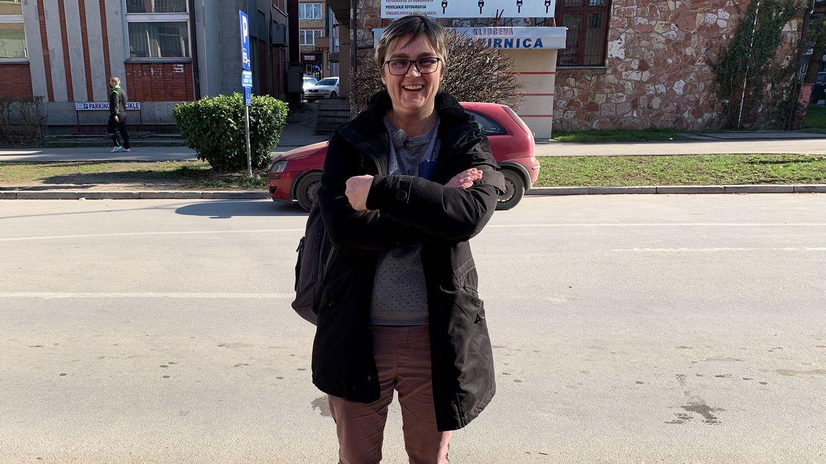 Eine Frau steht mit verschränkten Armen auf einer Straße.