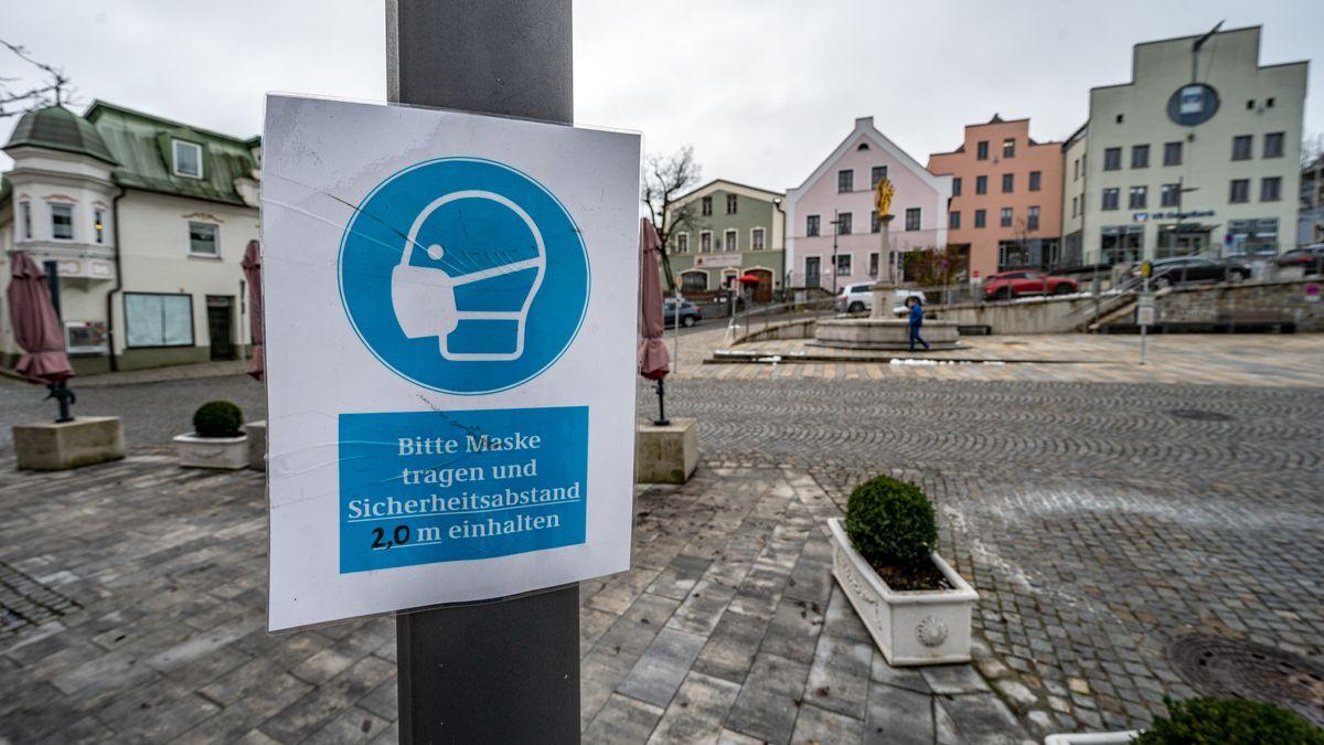 """""""Bitte Maske tragen und Sicherheitsabstand 2,0 m einhalten"""" steht auf einem Schild in der Innenstadt von Regen."""