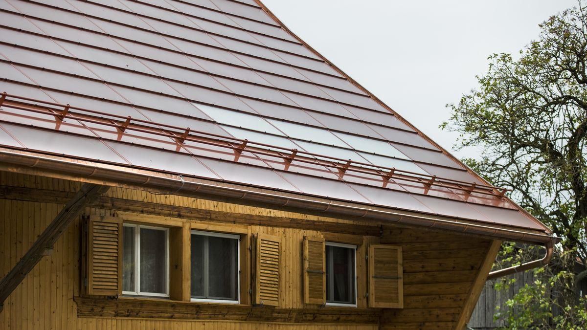 Solaranlage mit ziegelroten Photovoltaikmodulen auf dem Dach eines Bauernhauses in Ecuvillens