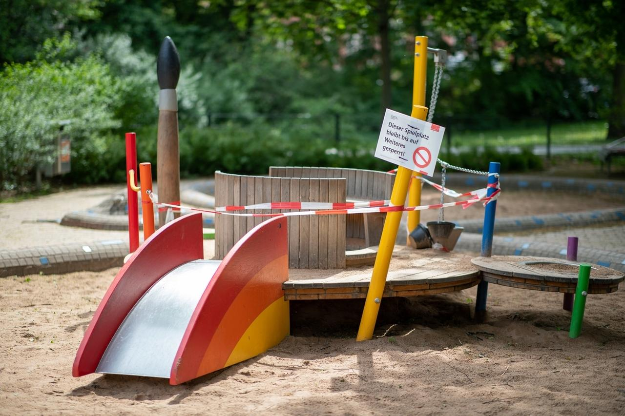05.05.2020, Bayern, Nürnberg: «Dieser Spielplatz bleibt bis auf Weiteres gesperrt» steht auf einem Schild der Stadt neben einem mit Absperrband behangenem Spielgerät auf einem Spielplatz. Nach wochenlanger Schließung wegen der Corona-Pandemie dürfen Spielplätze ab dem 6. Mai in Bayern wieder öffnen. Foto: Daniel Karmann/dpa +++ dpa-Bildfunk +++