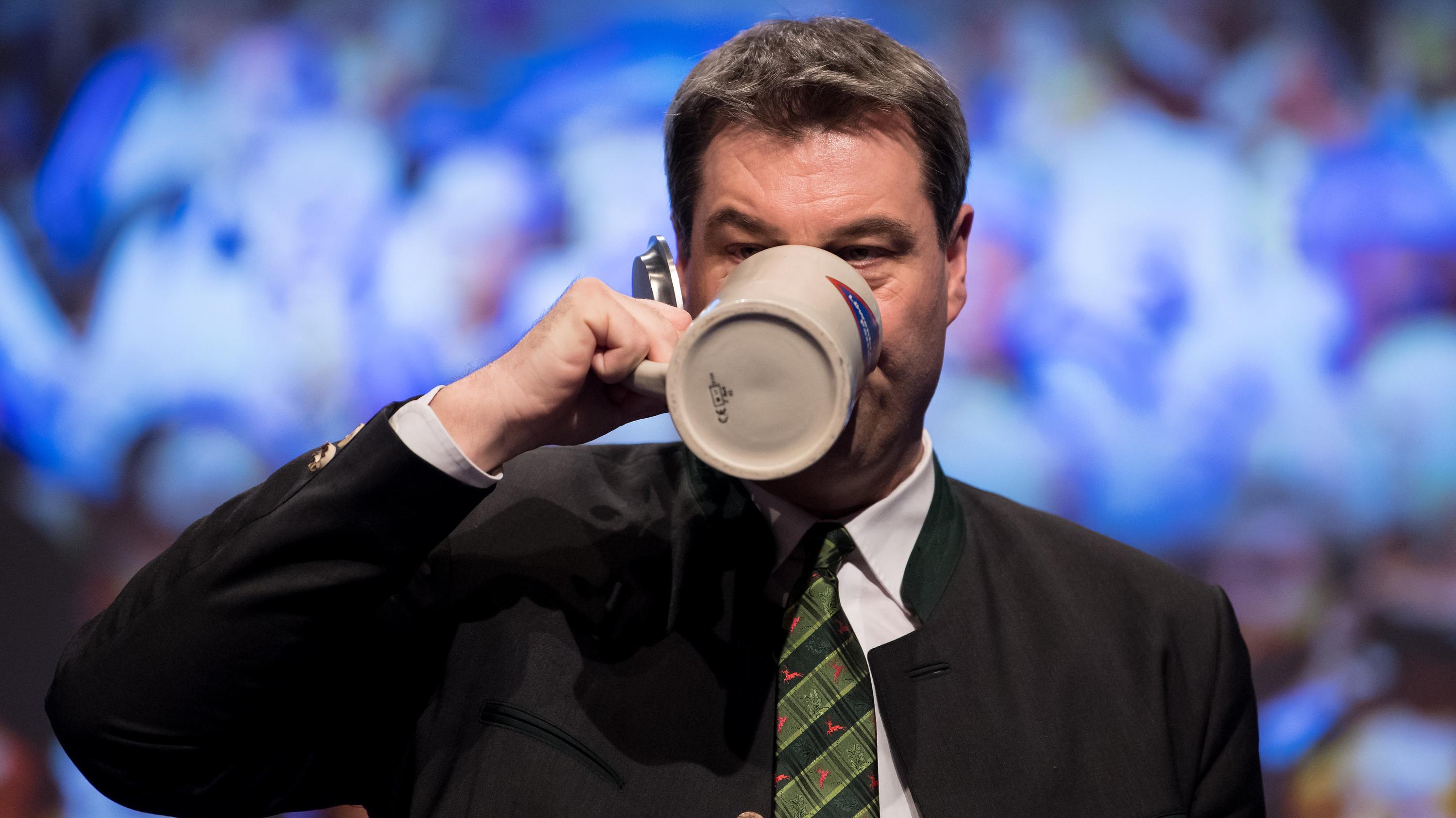 Markus Söder (CSU), damaliger Finanzminister von Bayern und amtierender Ministerpräsident, trinkt beim politischen Aschermittwoch der CSU nach seiner Rede ein Bier auf der Bühne.
