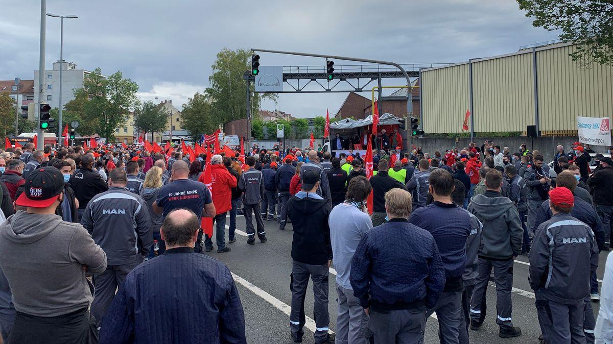 Menschen mit vielen roten Verdi-Fahnen vor dem Werkstor von MAN in Nürnberg.
