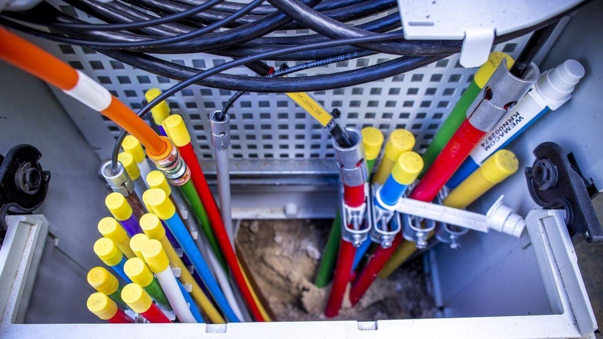 Durch farbige Leerrohre werden Glasfaserkabel zu Hausanschlüssen auf einer Baustelle für den Breitband-Internetausbau eingeblasen.