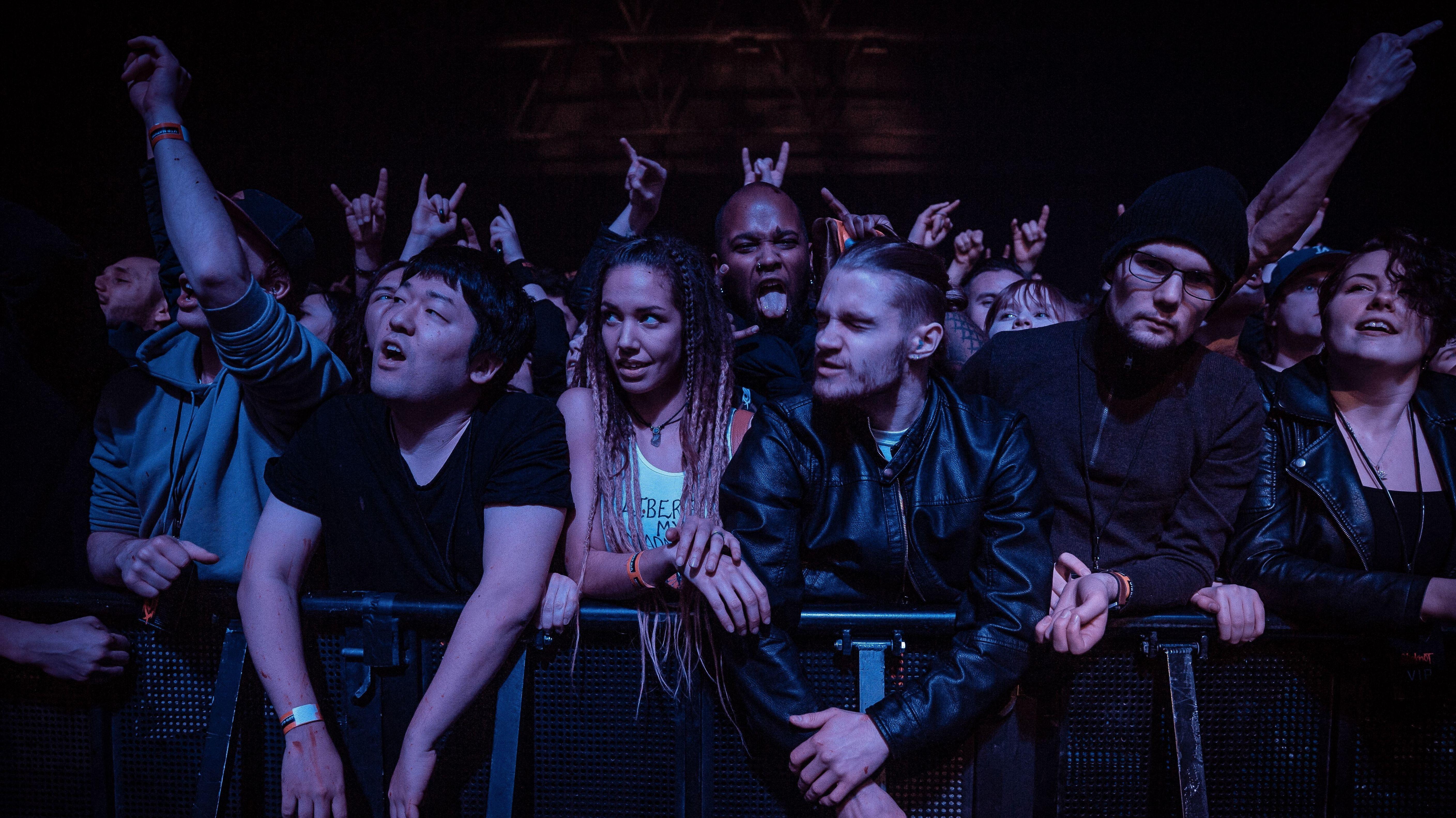 Fans bei einem Konzert der Band Slipknot, die sehr dicht gedrängt an einer Absperrung stehen.