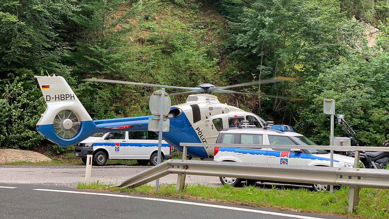 """Des Münchner Polizeihubschraubers """"Edelweiß 8"""" auf dem Parkplatz mit zwei weiteren Einsatzfahrzeugen"""
