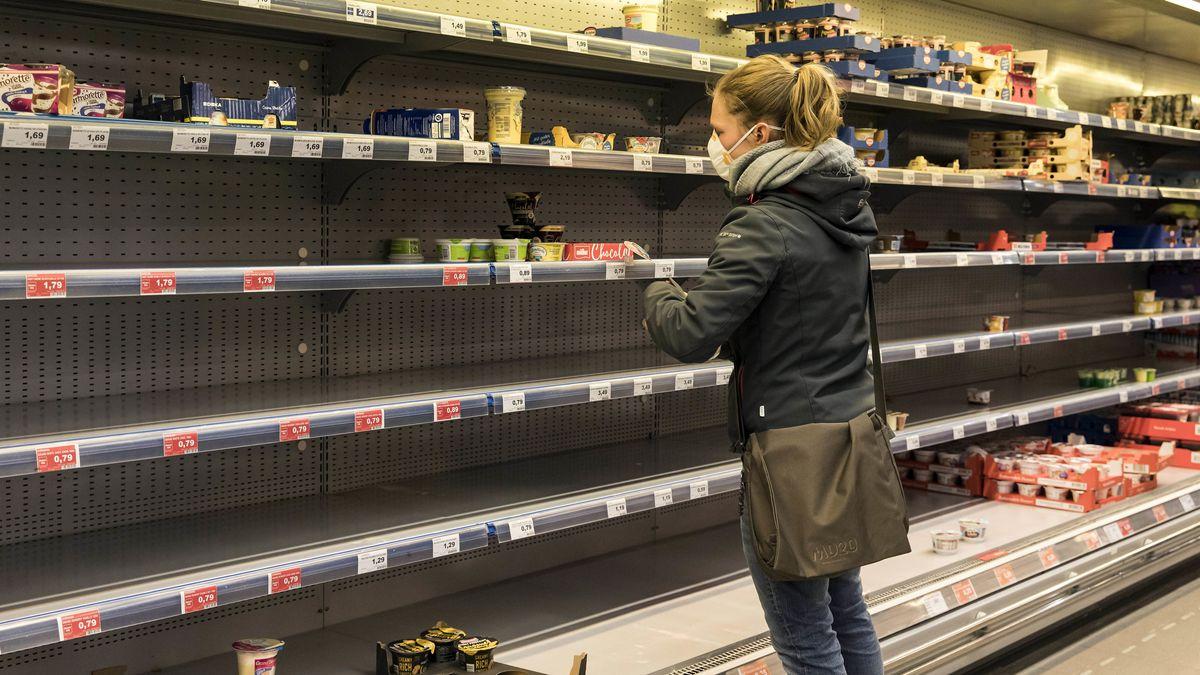 Eine junge Frau mit Mund-Nasen-Schutz steht vor einem weitgehend leeren Supermarktregal