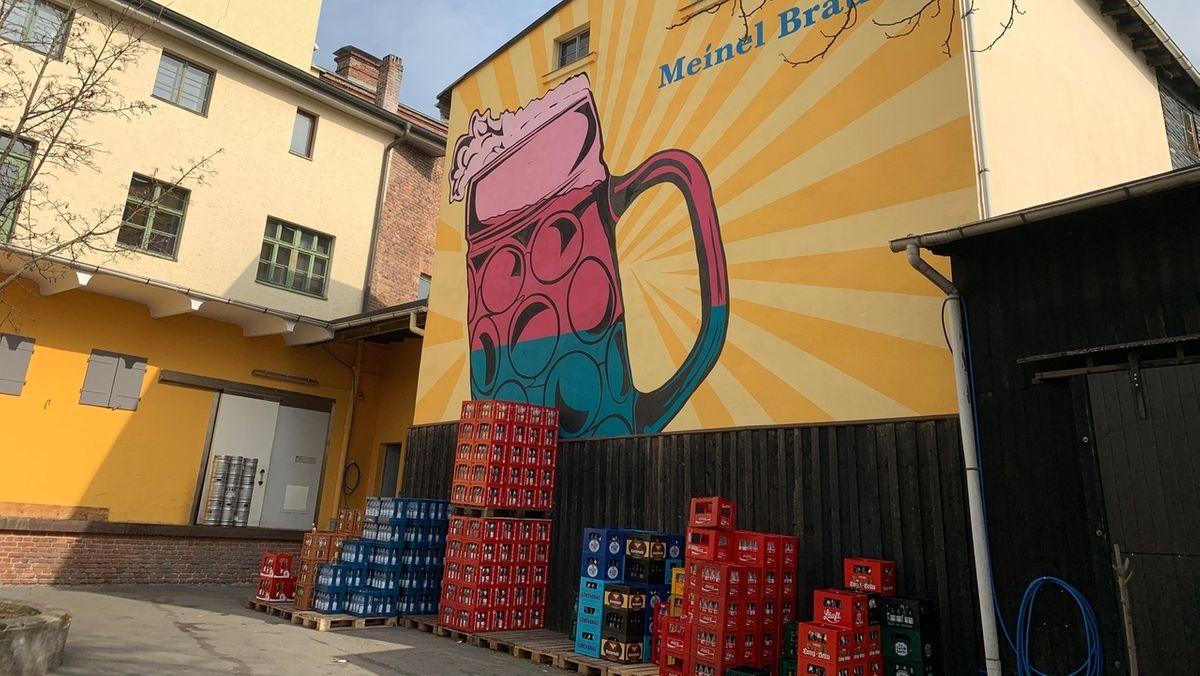 Bierkästen stehen vor einem Gebäude, das mit einem bunten Streetart-Gemälde verziert ist.