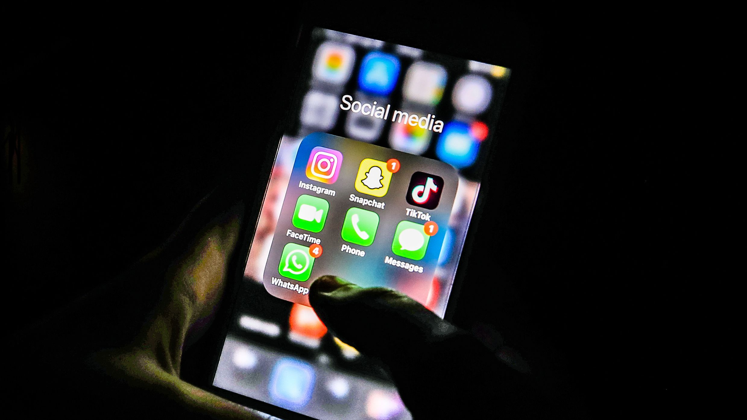 Jemand hält ein Smartphone in der Hand, auf dem Social Media-Apps zu sehen sind.
