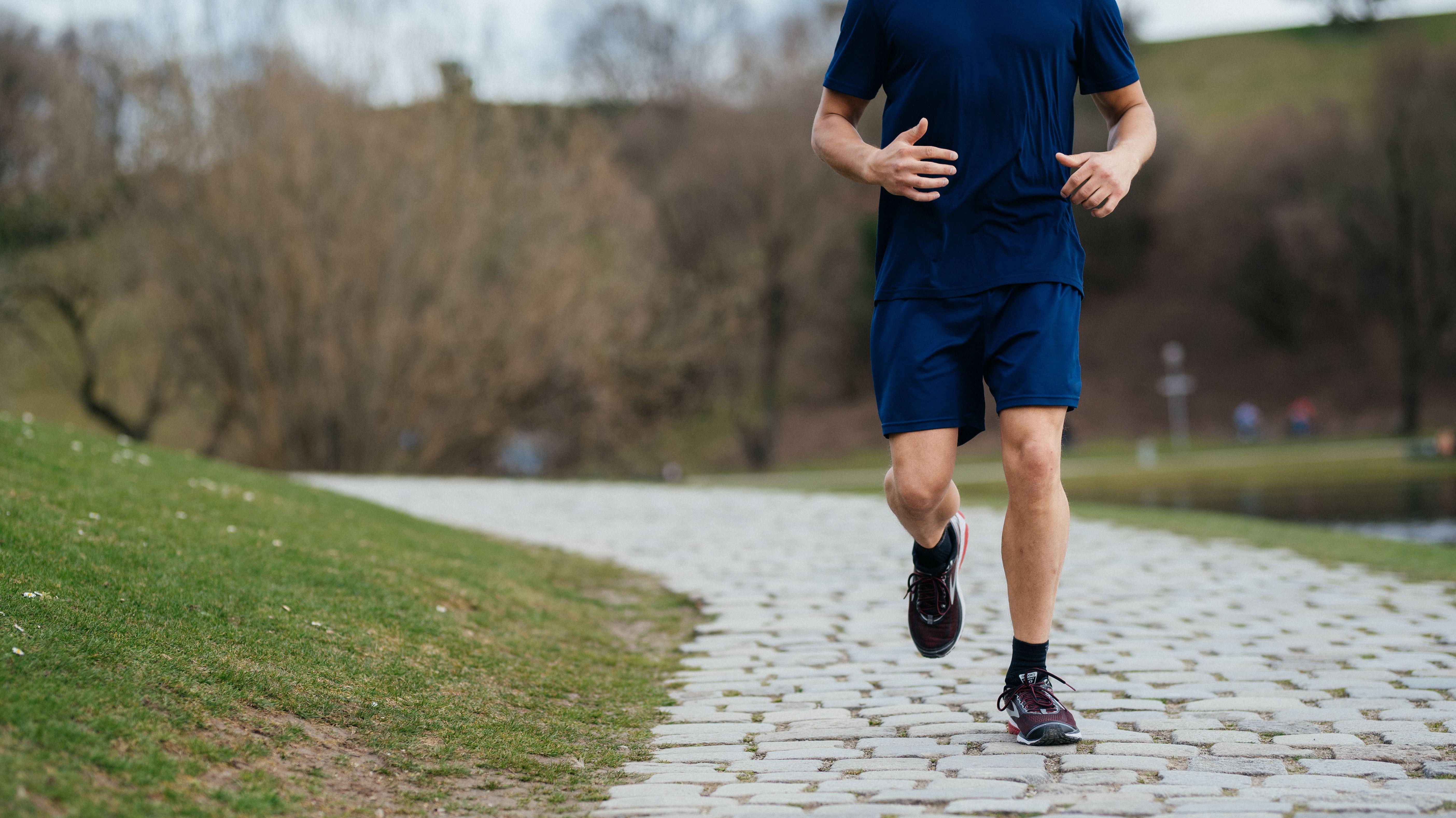 Ein Mann läuft in Joggingschuhen auf einem gepflasterten Weg