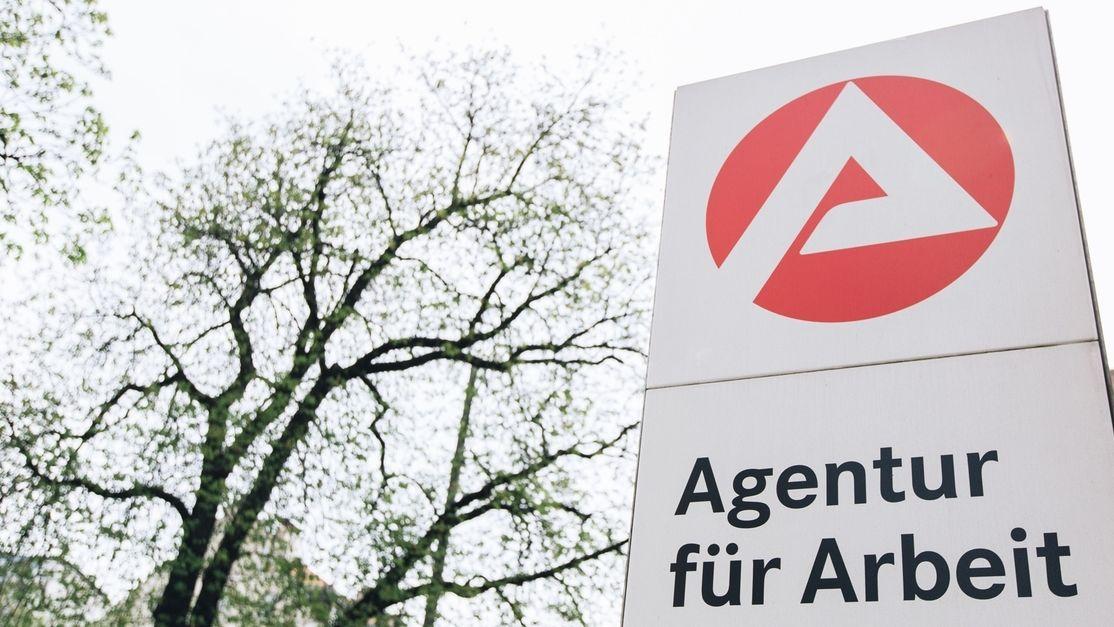 """Signet der Arbeitsagentur mit einem weißen """"A"""" auf rotem Hintergrund und dem Schriftzug """"Agentur für Arbeit"""" darunter."""