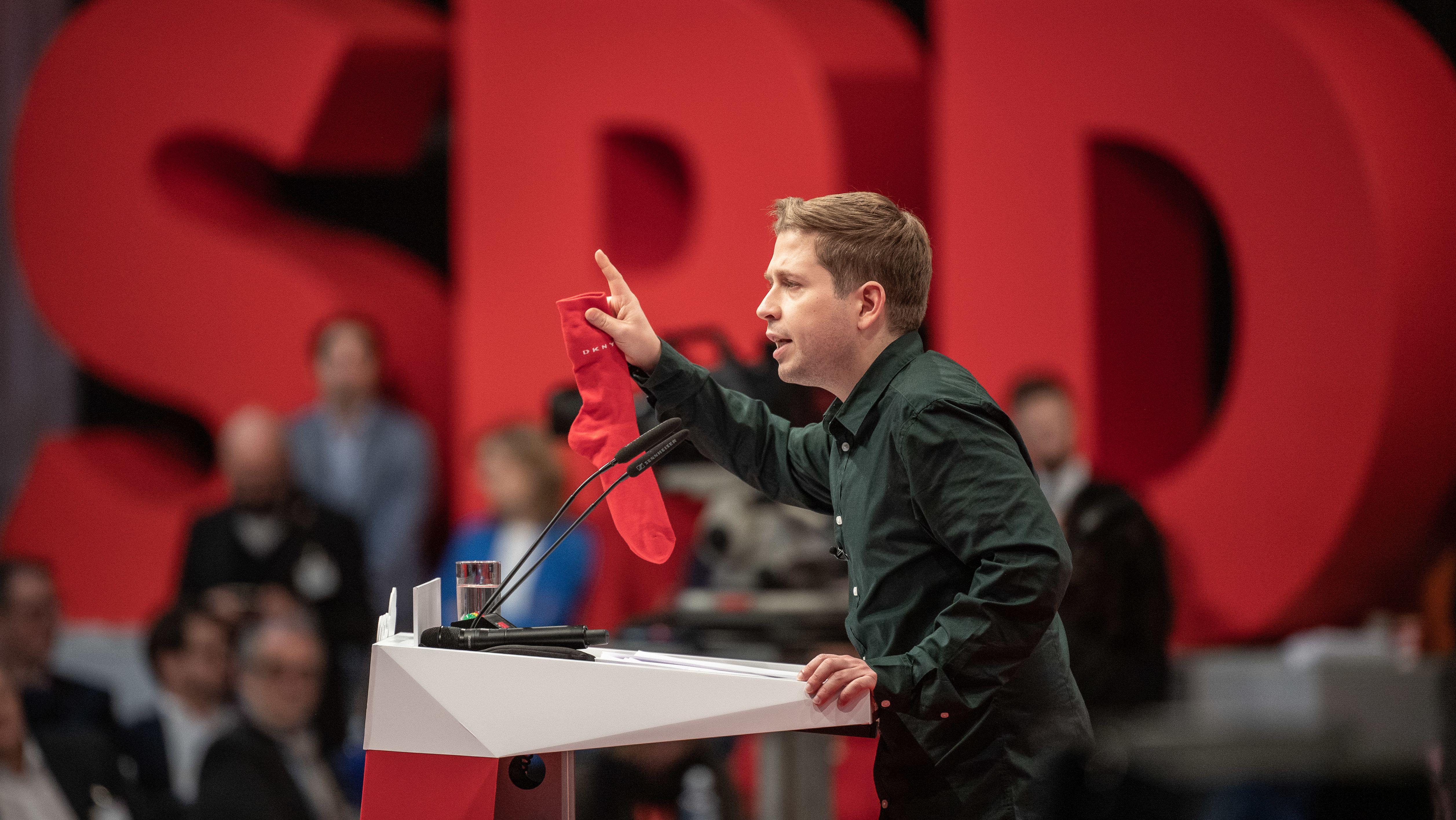 Kevin Kühnert, Bundesvorsitzender der Jusos, spricht mit einer roten Socke in der Hand beim SPD-Bundesparteitag