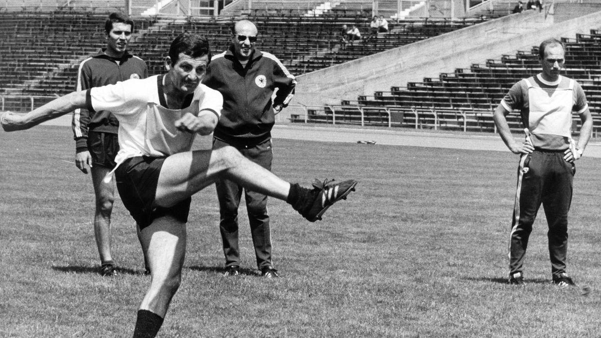 Der Nürnberger Ludwig Müller (v) schießt, Torhüter Jürgen Rynio (l, hinten), Bundestrainer Helmut Schön (M, hinten) und dessen Assistent Udo Lattek (r) schauen zu.