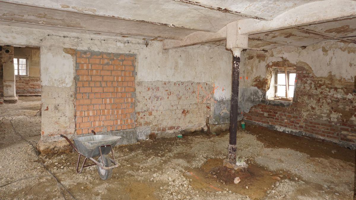Freigelegter Raum mit kahlen Wänden und Erdboden.
