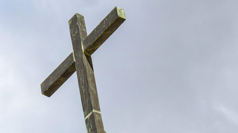 Christliches Kreuz in den Himmel gereckt (Symbolbild)