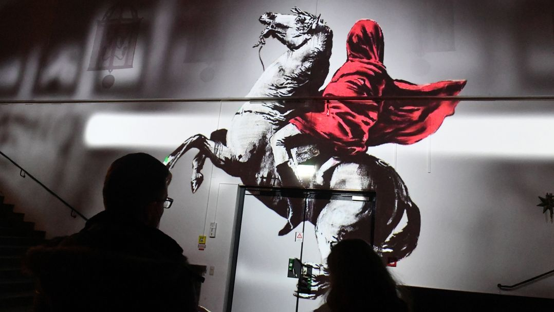 Person in rotem Umhang auf weißem Pferd.