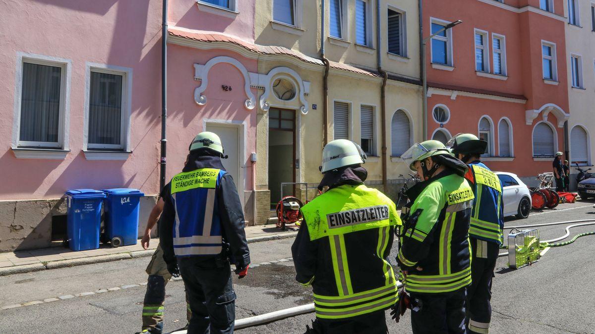 Einsatzkräfte der Feuerwehr vor dem Mehrfamilienhaus