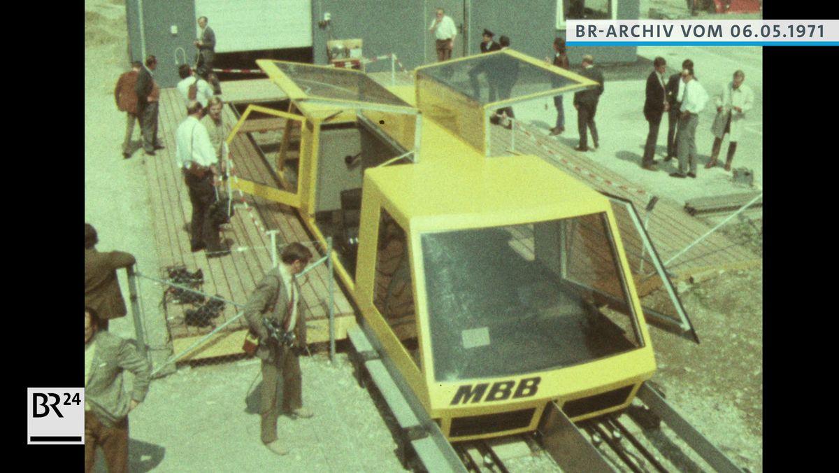 Menschen beim Betrachten der gelben Magnetschwebebahn von der Firma Messerschmitt-Bölkow-Blohm