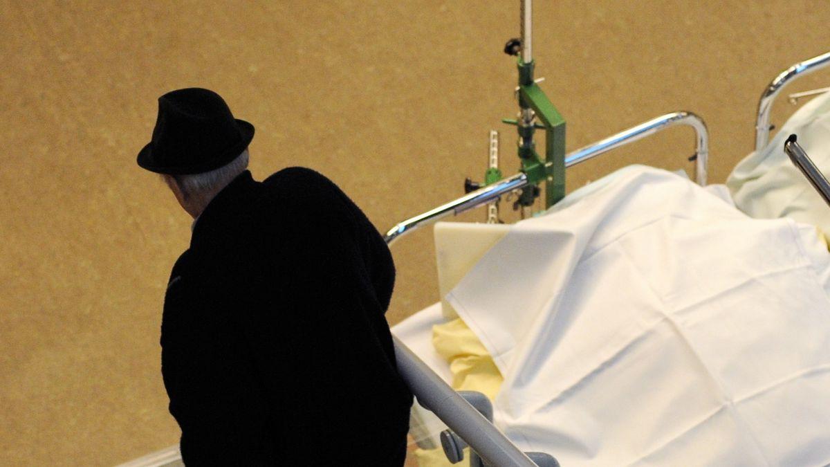 Ein älterer Mann geht im städtischen Krankenhaus Bogenhausen an einem Klinikbett vorbei.