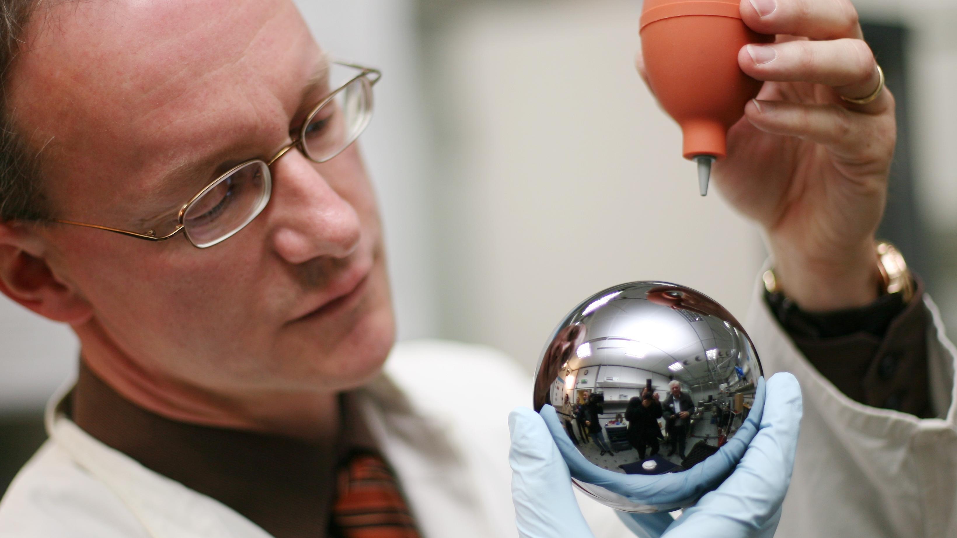 Ein Wissenschaftler von der Physikalisch-Technischen Bundesanstalt (PTB) entstaubt eine etwa eine Million Euro teure, etwa zehn Zentimeter dicke Kugel aus Silizium. Die Anzahl der Atome in dieser Kugel wird in Zukunft die Maßeinheit Kilogramm definieren.
